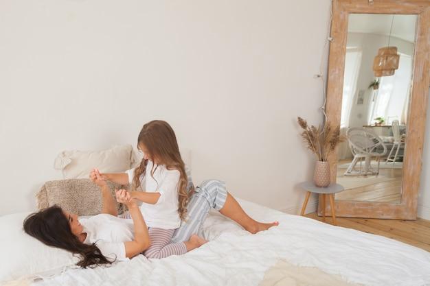 Glückliche liebende familie, die entspannend liegt und zusammen im schlafzimmer genießt Premium Fotos