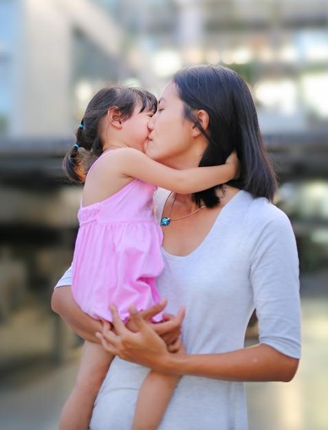 Glückliche liebevolle familie. mutter und kind mädchen küssen und umarmen Premium Fotos