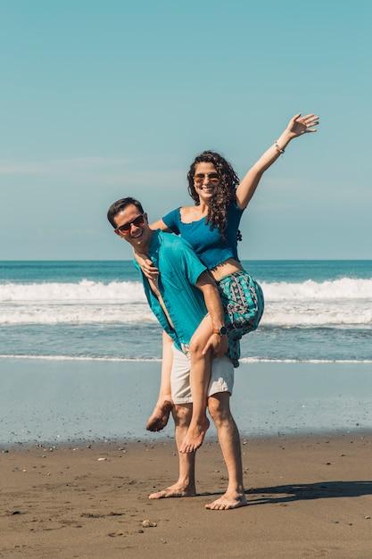 Glückliche liebevolle paare, die spaß auf sandigem strand des sommers haben Kostenlose Fotos