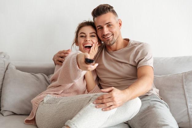 Glückliche liebevolle paare, die zusammen auf couch sitzen und fernsehen Kostenlose Fotos