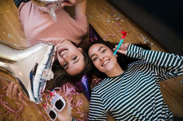 Glückliche mädchen der draufsicht, die auf den boden legen Kostenlose Fotos