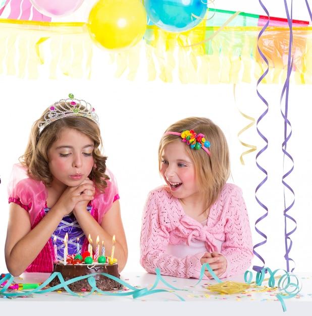 Glückliche mädchen der kinder, die geburtstagsfeierkuchen durchbrennen Premium Fotos
