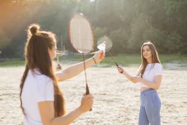 Glückliche mädchen des mittleren schusses, die badminton spielen Kostenlose Fotos