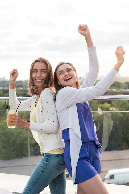 Glückliche mädchen tanzen rücken an rücken Kostenlose Fotos