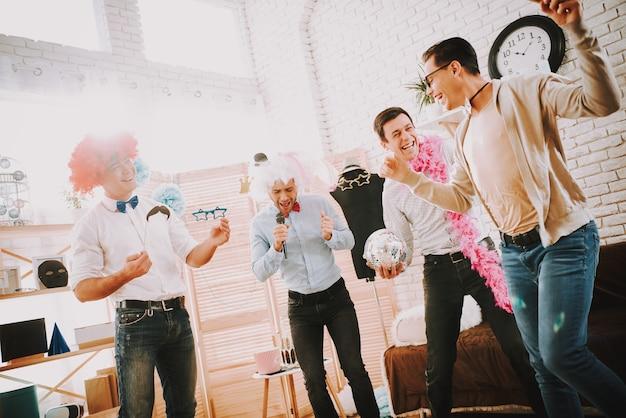 Glückliche männer mit fliegen karaoke-lieder auf party singen. Premium Fotos