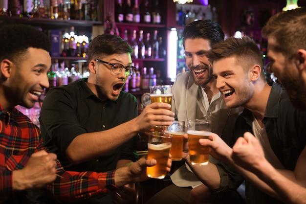 Glückliche männliche freunde, die mit bierkrügen in der kneipe klirren Kostenlose Fotos