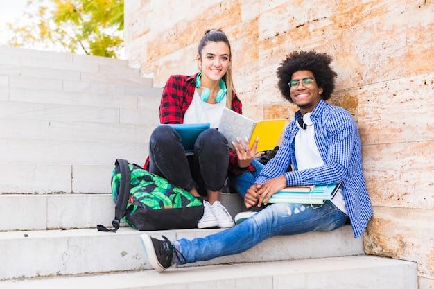 Glückliche männliche und weibliche hochschulstudenten, die auf dem treppenhaus schaut zur kamera sitzen Kostenlose Fotos