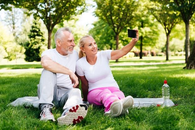 Glückliche menschen des vollen schusses, die draußen selfies nehmen Kostenlose Fotos