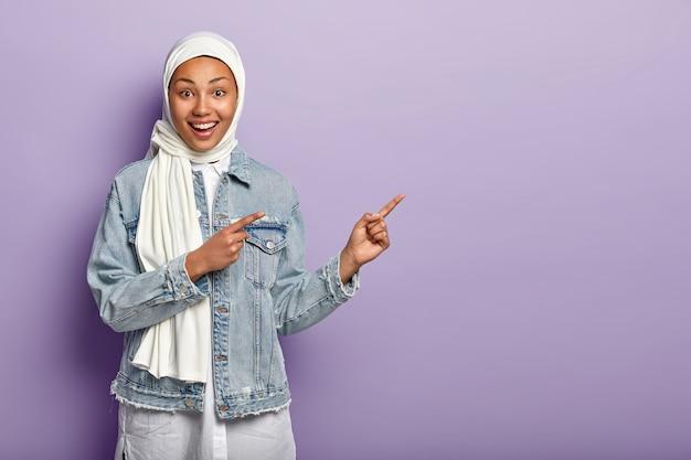 Glückliche mischlingsfrau hat fröhlichen ausdruck, zeigt mit beiden vorderfingern weg, sagt dort folgen, zeigt richtung über kopierraum, trägt jeanskleidung, weißen hijab, isoliert auf lila wand Kostenlose Fotos