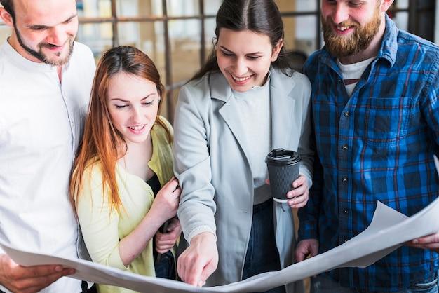 Glückliche mitarbeiter, die an blaupause im büro arbeiten Kostenlose Fotos