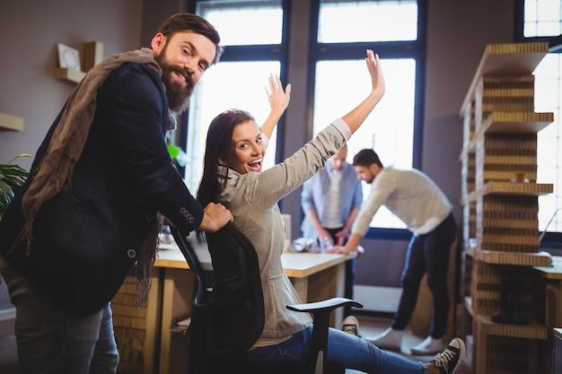 Glückliche mitarbeiter, die durch schreibtisch im kreativen büro genießen Premium Fotos