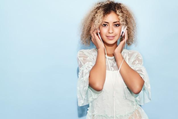 Glückliche modefrau mit blonder afro-frisur, die lächelt und musik in kopfhörern hört Kostenlose Fotos