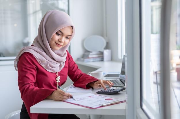 Glückliche moderne asiatische moslemische geschäftsfrau, die an schreibtisch arbeitet. Premium Fotos