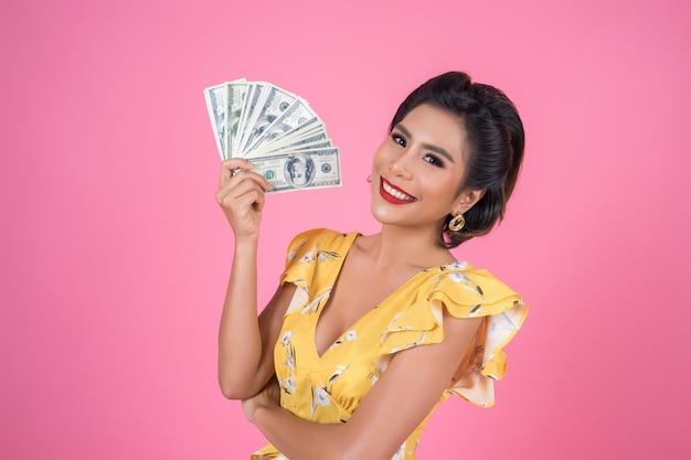 Glückliche modeschönheitshand, die dollargeld hält Kostenlose Fotos