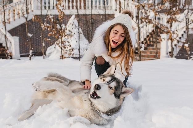 Glückliche momente auf winterzeit der erstaunlichen youful frau, die mit husky hund im schnee spielt. helle positive emotionen, wahre freundschaft, liebe zu haustieren, beste freunde, lächeln, spaß haben, winterferien. Kostenlose Fotos