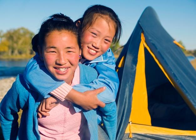 Glückliche mongolische mädchen, die piggyback am campingplatz spielen. Kostenlose Fotos