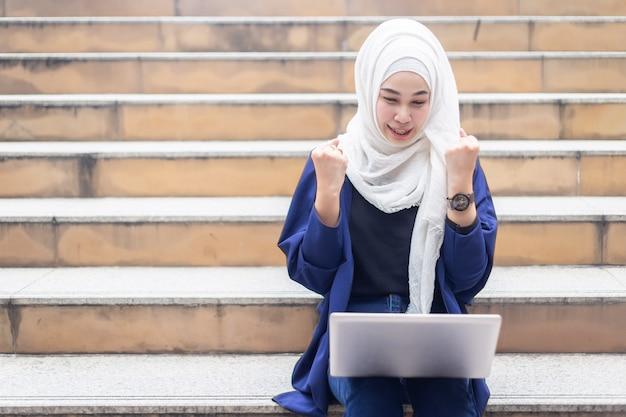 Glückliche moslemische geschäftsfrauen im hijab mit dem laptop, der draußen arbeitet. Premium Fotos