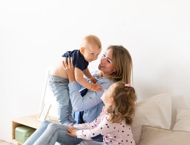 Glückliche mutter der seitenansicht, die mit ihren kindern spielt Kostenlose Fotos