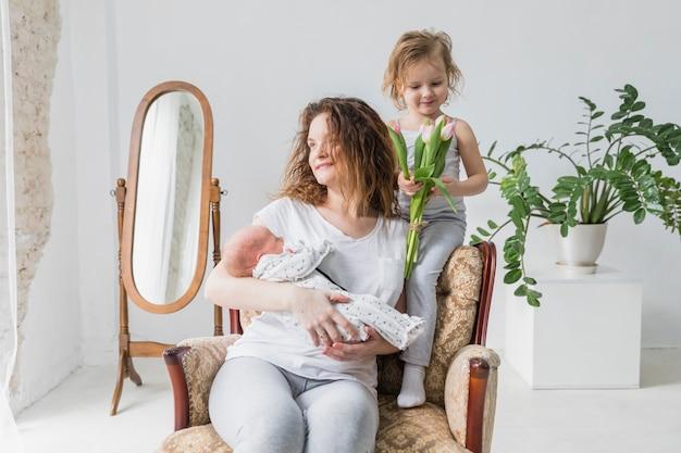 Glückliche mutter, die auf sessel mit ihrem netten kind zwei im haus sitzt Kostenlose Fotos