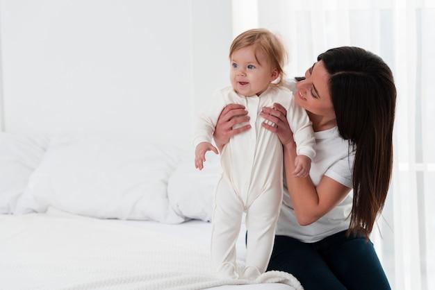 Glückliche mutter, die baby im bett hält Kostenlose Fotos