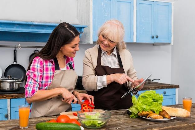 Glückliche mutter, die ihre junge tochter für das zubereiten des lebensmittels in der küche unterstützt Kostenlose Fotos
