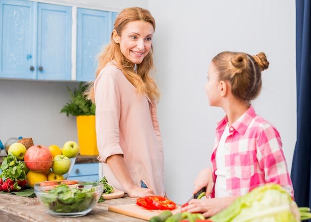 Glückliche mutter, die ihre tochter zubereitet den salat in der küche betrachtet Kostenlose Fotos