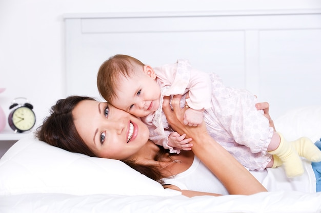 Glückliche mutter, die mit baby liegt Kostenlose Fotos