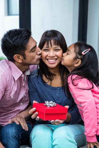 Glückliche mutter, die von ihren kindern beim halten eines geschenkes geküsst wird Premium Fotos