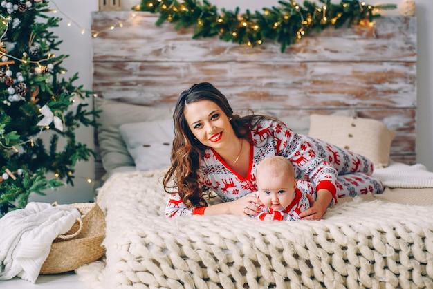 Glückliche mutter mit ihrer kleinen tochter in der feiertagskleidung mit den druckrotwild und schneeflocken, die spaß auf dem bett im gemütlichen raum mit einem weihnachtsbaum und weihnachtslichtern haben. neujahr und weihnachten konzept. Premium Fotos