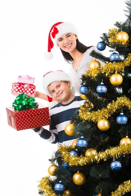Glückliche mutter mit kind halten schachtel mit geschenk nahe dem weihnachtsbaum Kostenlose Fotos
