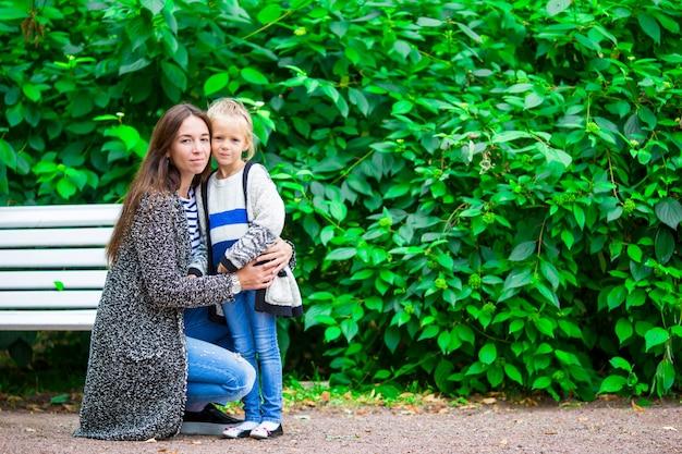 Glückliche mutter und entzückendes kleines mädchen, die warmes wetter am schönen park genießt Premium Fotos