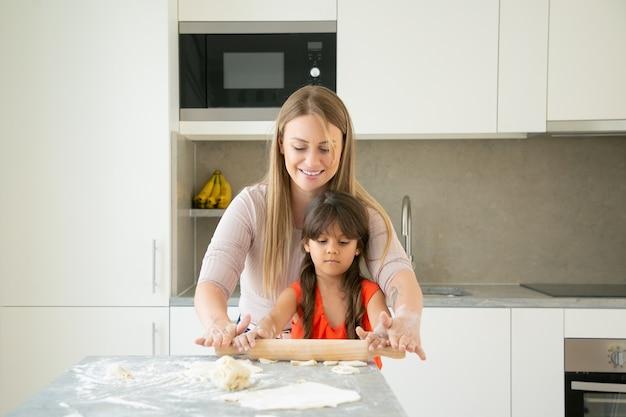 Glückliche mutter und ihr mädchen genießen zeit zusammen, teig auf küchentisch mit mehlpulver rollend. Kostenlose Fotos