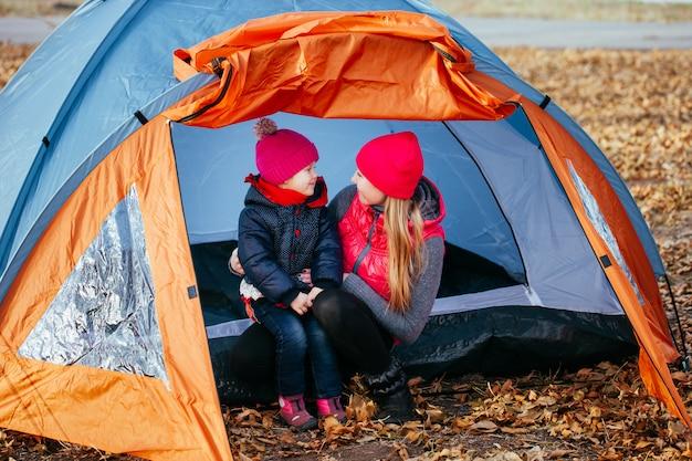 Glückliche mutter und ihre tochter, die das sitzen in einem zelt aufwirft Premium Fotos