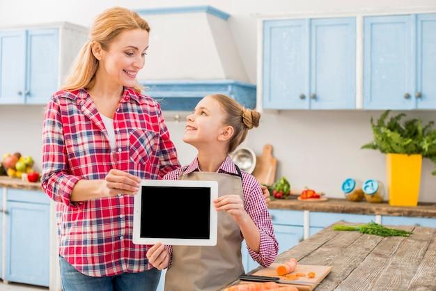 Glückliche mutter und tochter, die in der hand die digitale tablette einander betrachtend hält Kostenlose Fotos