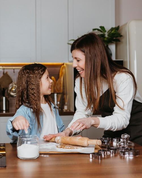 Glückliche mutter und tochter, die in der küche zu hause kochen Kostenlose Fotos