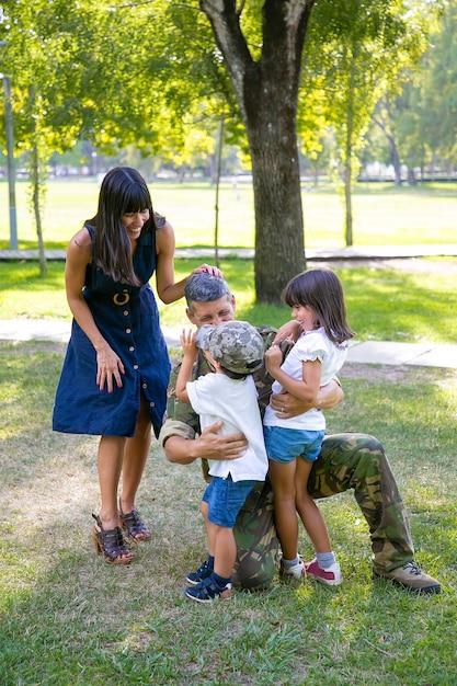 Glückliche mutter und zwei kinder, die militärischen vater in tarnuniform im freien umarmen. vertikaler schuss. familientreffen oder rückkehr nach hause konzept Kostenlose Fotos