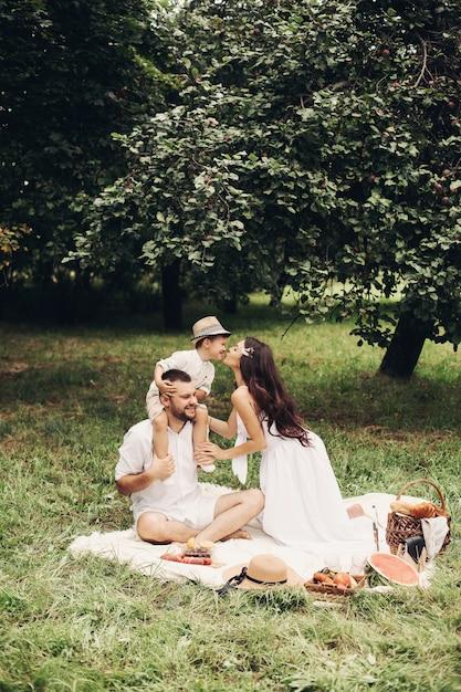Glückliche mutter, vater und ihr süßer kleiner sohn machen picknick im sommerpark. kind sitzt auf den schultern seines vaters. familien- und freizeitkonzept Premium Fotos