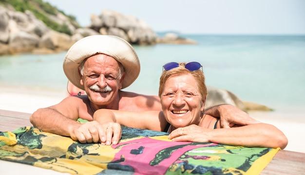 Glückliche paare im ruhestand, die für reisefoto am tropischen strand aufwerfen Premium Fotos