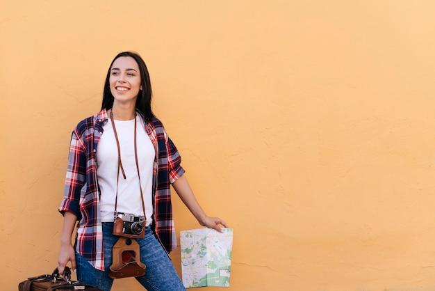 Glückliche recht junge frau, welche die tasche und karte stehen nahe pfirsichwand hält Kostenlose Fotos
