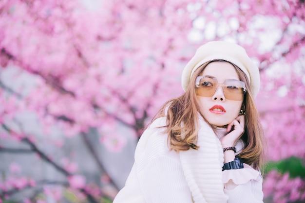 Glückliche reisefrau und -lächeln mit kirschblüte-kirschblütenbaum im urlaub während frühling, asiatisch Premium Fotos