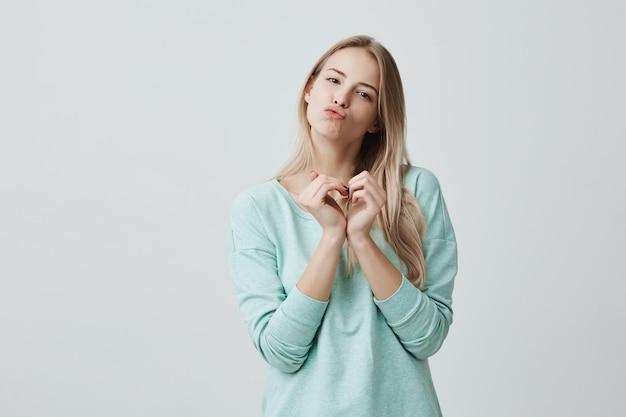 Glückliche reizende frau mit blondem langem haar, das liebeszeichen mit ihren in herzform hohlen händen zeigt. kaukasische frau in der liebe schmollende lippen, küsse senden, positive emotionen ausstrahlen. Kostenlose Fotos
