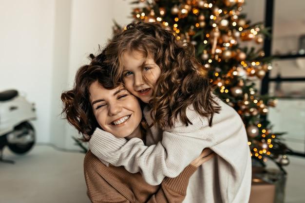 Glückliche reizende frau mit ihrer kleinen süßen tochter mit welligem haar, das spaß vor weihnachtsbaum umarmt und spaß macht Kostenlose Fotos