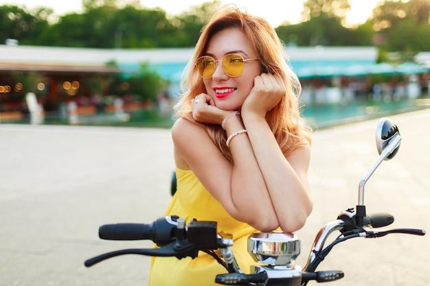 Glückliche rothaarige frau im gelben kleid, das auf ihrem elektroroller entspannt, während urlaubszeit in der modernen stadt verbringt. romantische stimmung. Kostenlose Fotos