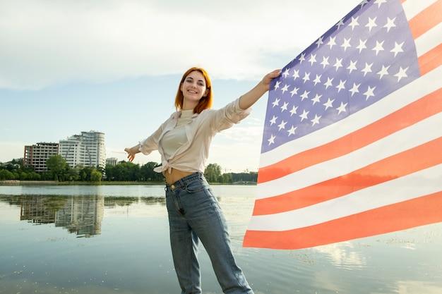 Glückliche rothaarige junge frau mit der nationalflagge der vereinigten staaten in ihrer hand. positives mädchen, das us-unabhängigkeitstag feiert. Premium Fotos