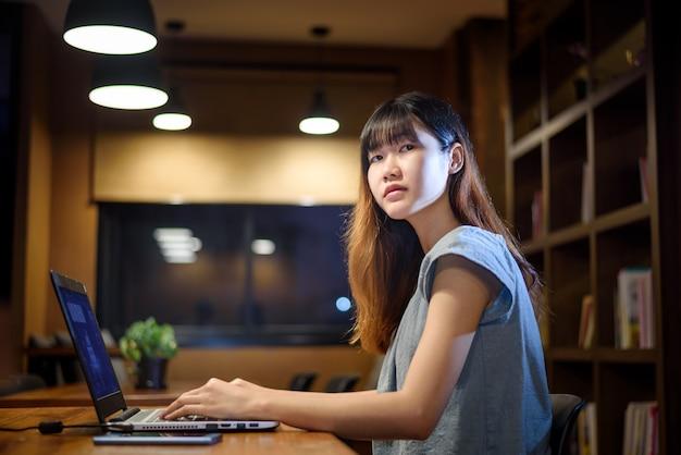Glückliche schöne asiatische studentenfrau, die an laptop im modernen bibliotheksraum arbeitet Premium Fotos