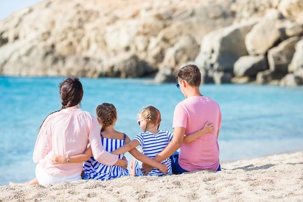 Glückliche schöne familie mit den kindern, die zusammen auf tropischen strand während der sommerferien gehen Premium Fotos