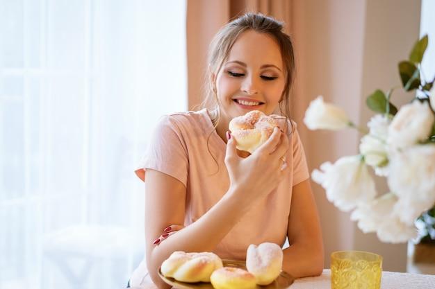 Glückliche schöne frau, die am tisch sitzt und einen kuchen hält Kostenlose Fotos