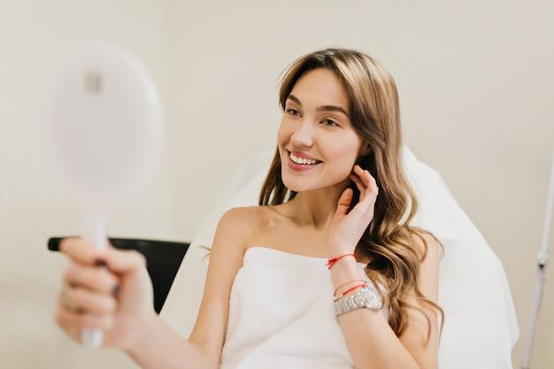 Glückliche schöne frau mit langen brünetten haaren nach kosmetiktherapie lächelnd, um im weißen raum zu spiegeln. freude, glück, gute ergebnisse, echte positive emotionen Kostenlose Fotos