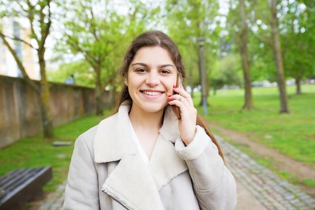 Glückliche schöne junge frau, die um telefon im park ersucht Kostenlose Fotos