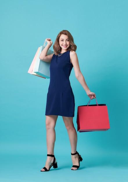 Glückliche schöne junge frau im blauen kleid und in der hand, die einkaufstasche lokalisiert über blauem hintergrund hält. Premium Fotos